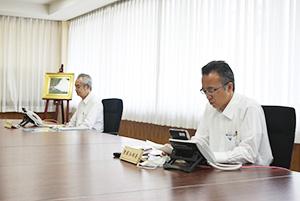 電話の前に座る中野委員長㊧と檜垣本部長