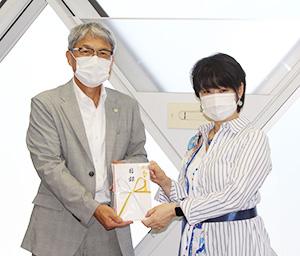 目録を手にする岡田代表取締役㊨と宮﨑教育長
