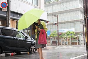 強い雨風の中、傘を傾けて歩く人(6日午後0時15分ごろ)