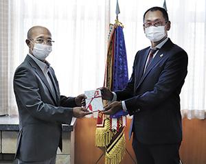 目録を手渡した井上事務局長㊨と愛須会長
