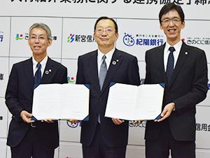 協定書を手に(左から)田谷理事長、松岡頭取、横田常務理事