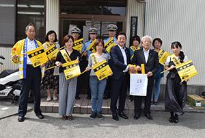 「横断中」の旗を手に藤本支店長(前列右から3人目)と新家支部長(同2人目)