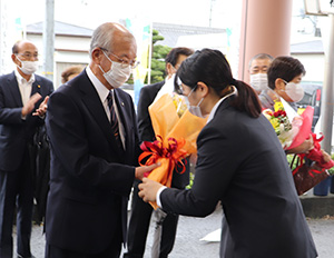 市職員から花束を受け取る中芝市長㊧