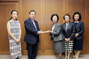 目録を手に澤学長(左から2人目)、玉置副会長(同3人目)ら