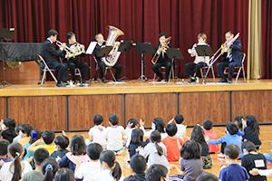 岩本校長(舞台右)が加わった「パプリカ」の演奏に手拍子をする児童ら(岡崎小)