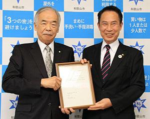 設置認可書を手にする寺下理事長㊧、尾花市長