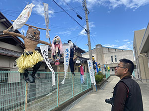 山口小学校に並ぶかかしを眺める平岡会長