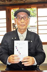 著書を手に津田さん