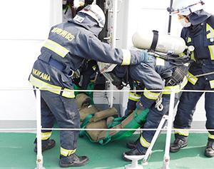 人形を担架に乗せて救出する消防署員