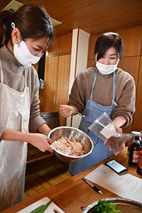 スパイスを使った料理を教える立畑さん㊨