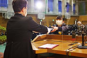 鈴木校長㊧から卒業証書を受け取る卒業生