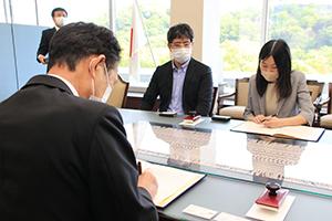 協定書に署名する尾花市長(手前)と浅賀代表取締役㊨、西CTO(左隣)