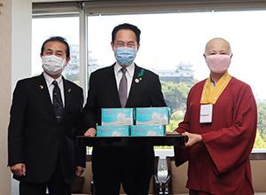寄贈されたマスクを手に尾花市長㊥、釋蓮花静香金剛上師㊨、遠藤市議(和歌山市提供)