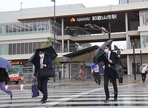雨が降る中、横断歩道を渡る人たち(17日午前9時ごろ、南海和歌山市駅前)