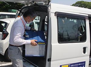 接種券入りの封筒を車両に積み込む和歌山市職員