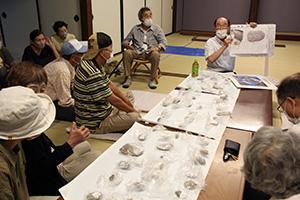 大小さまざまな経石を前に説明する小林さん(右奥)