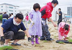 一生懸命植え付けをする児童や保護者ら