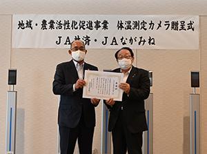 寄贈された体温計と角谷代表理事専務㊧、寺本町長