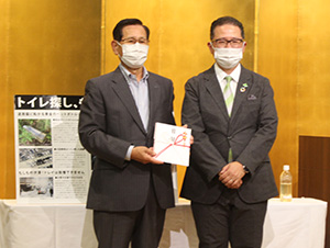 角谷社長㊨が阪本会長に目録を手渡した
