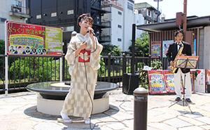 歌碑のそばで「和歌山ブルース」を歌う宮本さん㊧