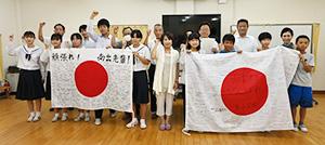 南出選手の母・美枝さん(中央)を囲み南出選手にエールを送る児童や生徒