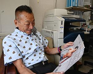 「広報かいなん」の南出選手の特集記事をうれしそうに眺める𠮷田館長